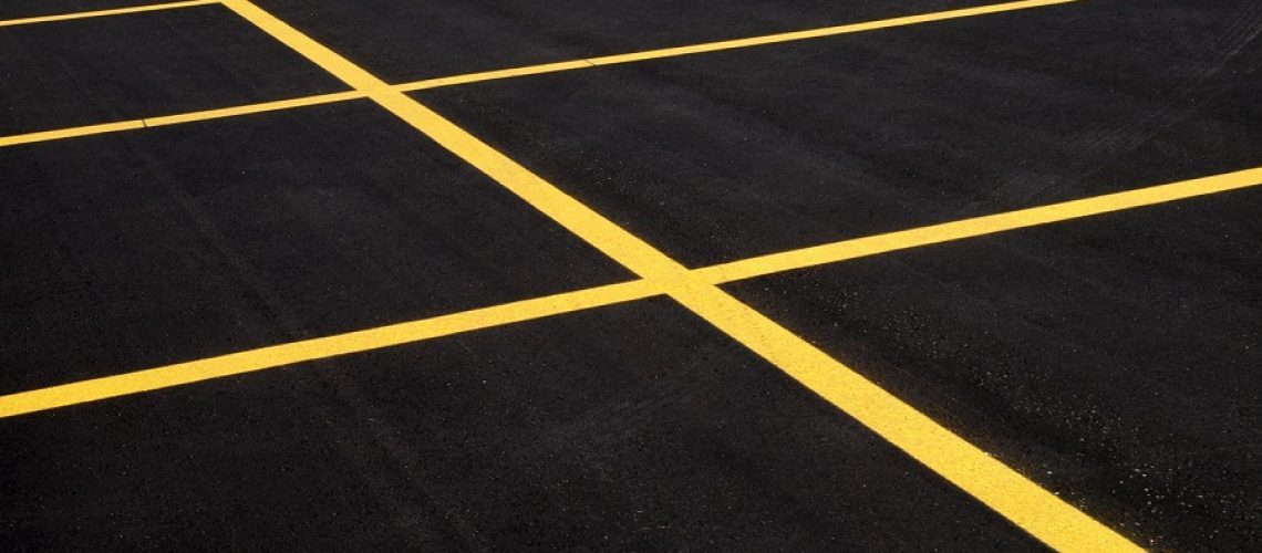A freshly paved & painted parking lot has everything but customers.