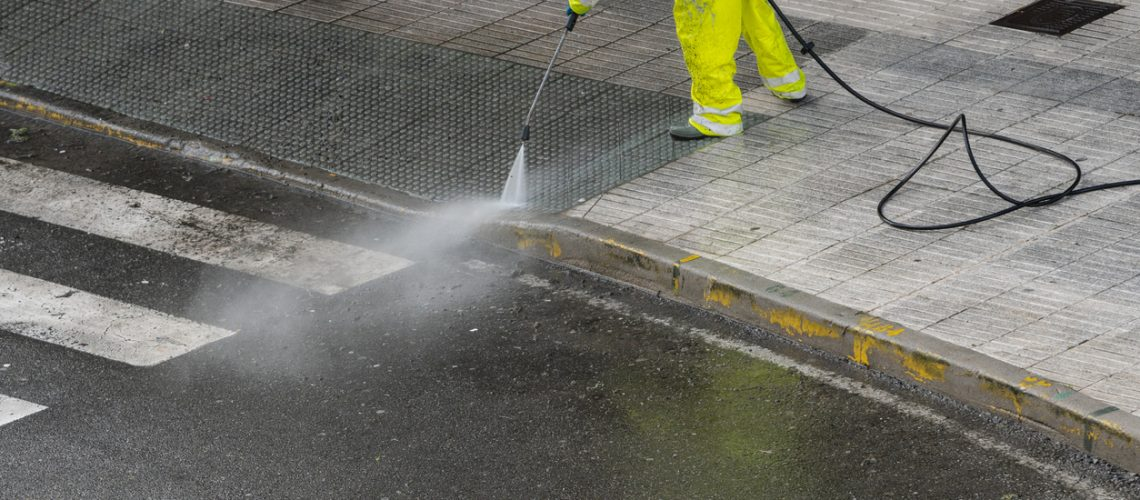 Worker cleaning the sidewalk with pressurized water